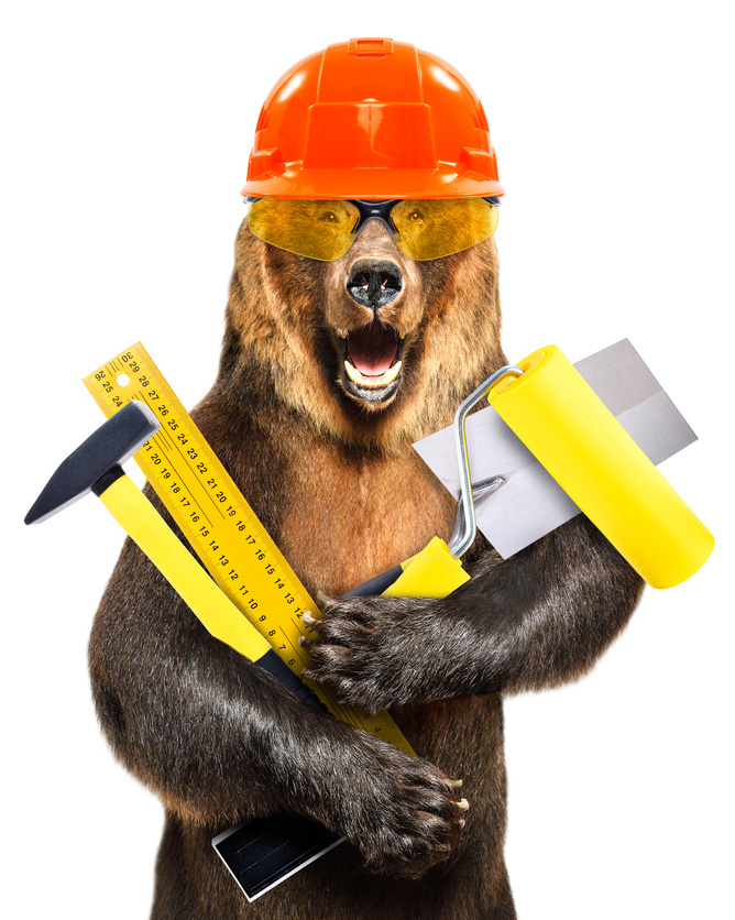 Portrait of a bear in a construction helmet with tools in hand isolated on white background